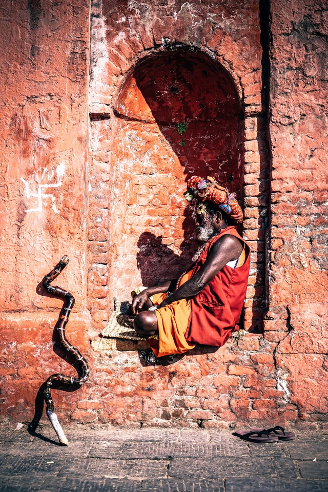 Indian man sitting on wall